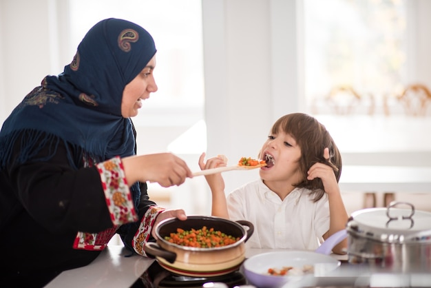 Traditionelle muslimische frau mit nettem kind im haus