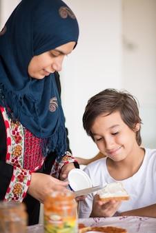 Traditionelle muslimische frau mit sohn in der küche Premium Fotos