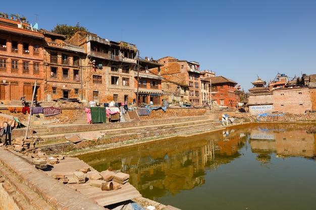 Traditionelle nepalesische newar-häuser nahe dem grünen teich in bhaktapur, nepal