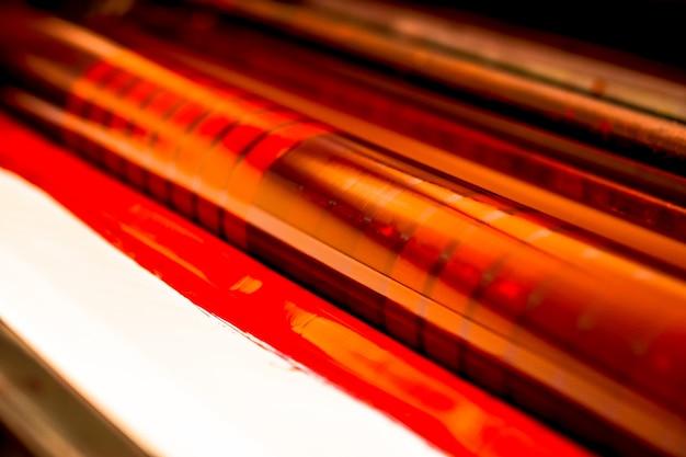 Traditionelle offsetdruckmaschine. drucken in tinte mit cmyk, cyan, magenta, gelb und schwarz. grafik, offsetdruck. abdruckwalze in offsetmaschine aus vier körpern magentafarbener tinte