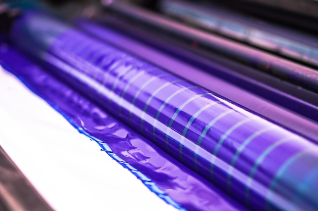 Traditionelle offsetdruckmaschine. drucken in tinte mit cmyk, cyan, magenta, gelb und schwarz. grafik, offsetdruck. detail der druckwalze in der offsetmaschine von vier körpern blauer tinte