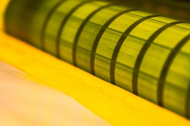 Traditionelle offsetdruckmaschine. drucken in tinte mit cmyk, cyan, magenta, gelb und schwarz. grafik, offsetdruck. detail der druckwalze in der offsetmaschine von vier körpern gelber tinte