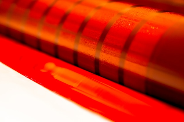 Traditionelle offsetdruckmaschine. drucken in tinte mit cmyk, cyan, magenta, gelb und schwarz. grafik, offsetdruck. detail einer druckwalze in einer magenta-offsetmaschine mit vier körpern
