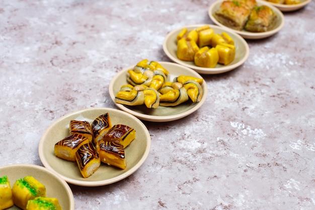 Traditionelle orientalische bonbons mit verschiedenen nüssen auf betondecke, draufsicht, kopienraum