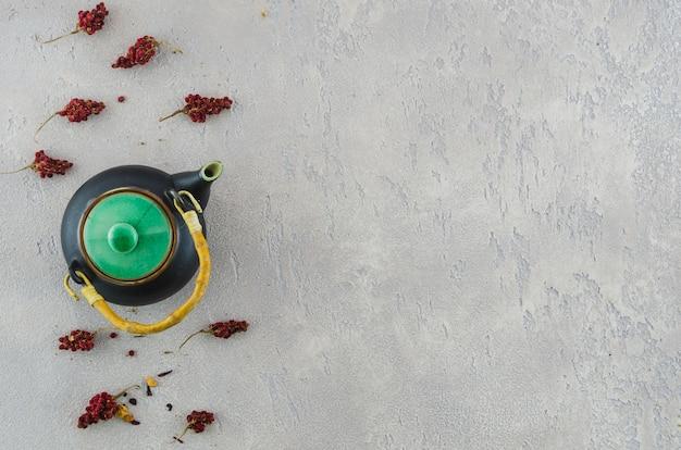 Traditionelle orientalische teekanne mit trockenblumekräutern auf grauem strukturiertem hintergrund