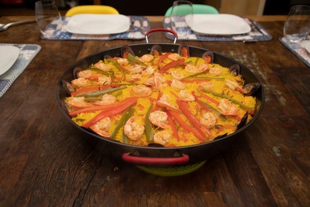 Traditionelle paella mit meeresfrüchten in der pfanne auf einem alten holztisch.