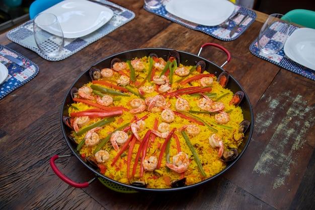 Traditionelle paella mit meeresfrüchten in der pfanne auf einem alten holztisch