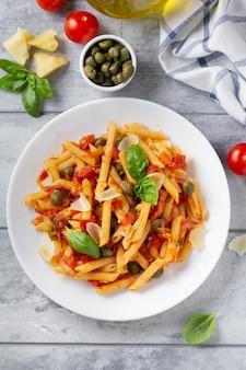 Traditionelle pasta putanesca mit tomatensauce (kapern, zwiebeln, knoblauch, sardellen)