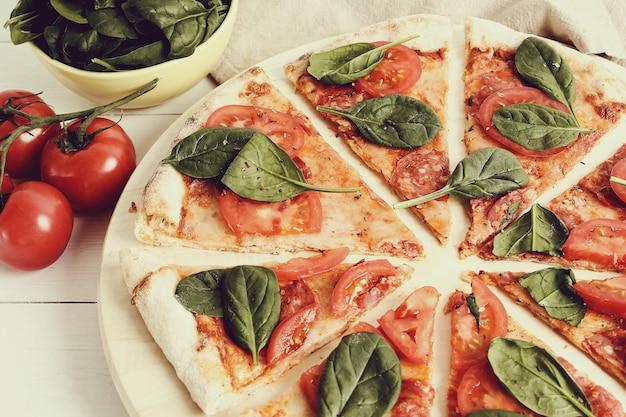 Traditionelle pizza mit tomatenscheiben und basilikumblättern