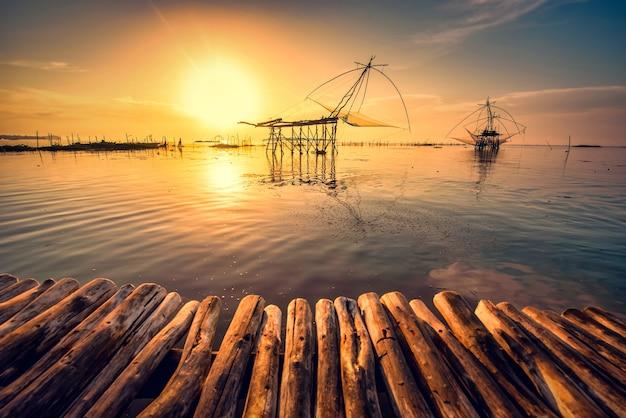 Traditionelle quadratische netzausrüstung bei sonnenaufgang im pakpra-kanal, phatthalung, thailand