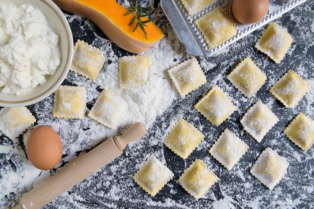Traditionelle rohe ravioli mit kürbis auf einem holztisch mit mehl, handgemacht, garprozess