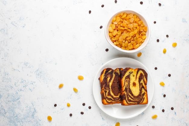 Traditionelle rosinenmarmorkuchenscheiben mit rosinen und kakaopulver, draufsicht
