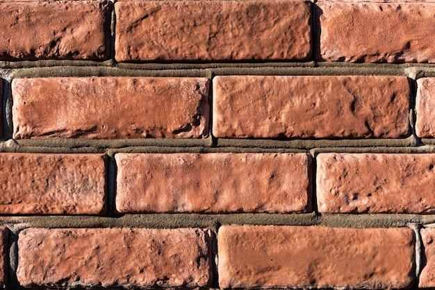 Traditionelle rote backsteinmauer mit weichem licht von links und einer oberfläche mit zement zwischen den ziegeln.