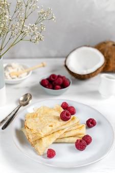 Traditionelle russische blini-pfannkuchen, französische crepes, serviert mit frischen himbeeren und kokosnuss