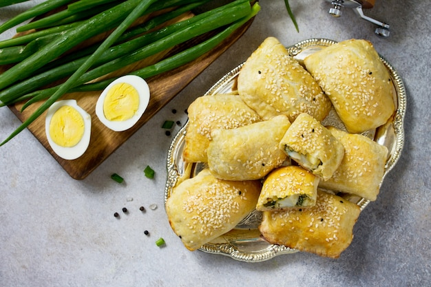 Traditionelle russische küche pies ei und frühlingszwiebeln auf hellem steintisch draufsicht flach
