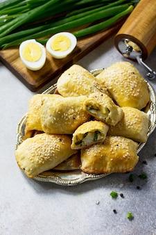 Traditionelle russische küche pies ei und frühlingszwiebeln auf hellem steintisch