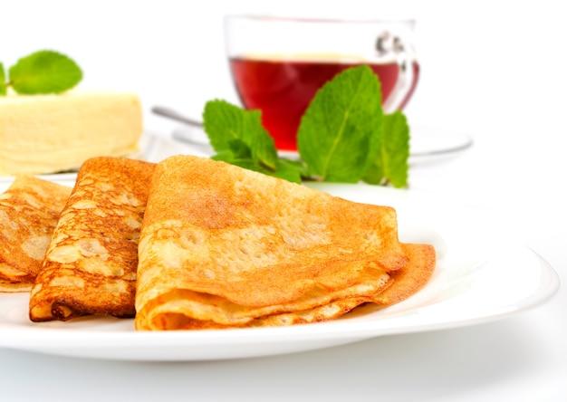 Traditionelle russische pfannkuchen mit minzblättern verziert. eine tasse schwarzen tee und kuchenbutter.
