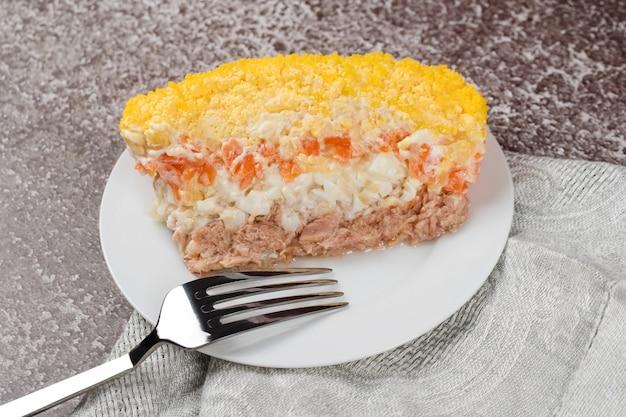Traditionelle russische salat mimose mit gemüse und fisch. schichtsalat mit kartoffeln, thunfisch, karotten, zwiebeln, eiern und mayonnaise.