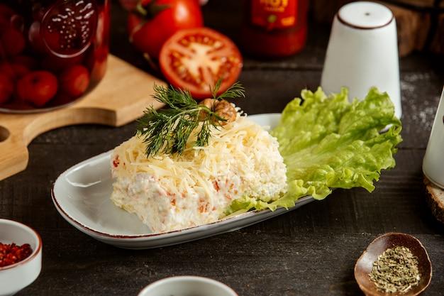 Traditionelle russische salatmimose der seitenansicht auf salat in der weißen schüssel