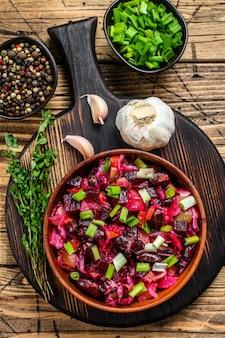 Traditionelle russische salatvinaigrette mit gekochtem gemüse, eingelegten gurken in der schüssel. hölzerner hintergrund. ansicht von oben.