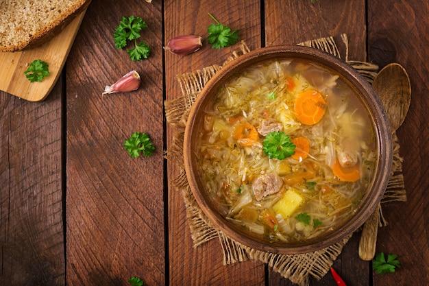 Traditionelle russische suppe mit kohl - sauerkrautsuppe. flach legen. draufsicht