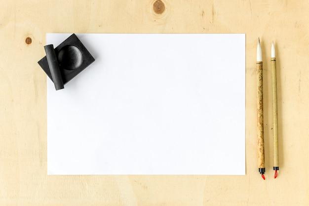 Traditionelle schreibensbürste der nahaufnahme japan auf holztisch. draufsicht und über licht
