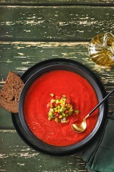 Traditionelle spanische kalte tomatensuppe von frischem rohem gemüse mit kochzutaten auf einem holztisch
