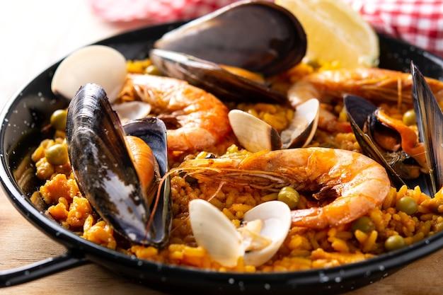 Traditionelle spanische paella mit meeresfrüchten auf holztisch