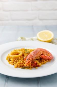 Traditionelle spanische paella mit meeresfrüchten und gemüse, serviert auf einem teller und auf einem blauen tisch