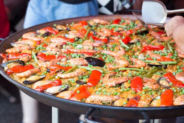 Traditionelle spanische reispaella mit meeresfrüchten. gemischter meeresfrüchteaufruhr gebraten würzig und salat. würzige meeresfrüchte.