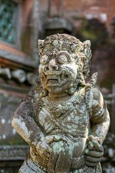 Traditionelle steinstatue mit dämon, gott und balinesischen mythologischen gottheiten in ubud, insel bali, indonesien, nahaufnahme. steinstatue hand mit feigenzeichen