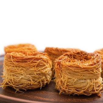 Traditionelle süßigkeiten mit honig und nüssen erdnüssen. frischer gebackener süßer ostnachtisch. süße brötchen aus dünnem teig. tiefenschärfe.