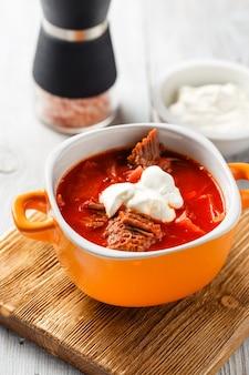Traditionelle suppe der russischen und ukrainischen küche borschtsch. fleischsuppe mit rüben in einer orangefarbenen schüssel auf einem leichten holzbrett.
