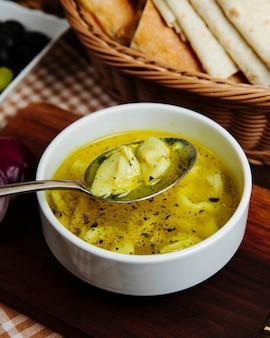 Traditionelle suppe dushbara knödel mit fleisch hammel essig koriander minze seitenansicht