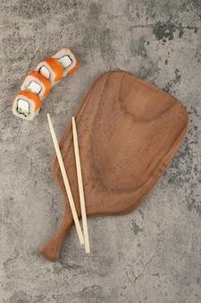 Traditionelle sushi-rollen und stäbchen rund um ein holzbrett