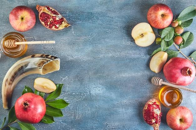Traditionelle symbole: honigglas und frische äpfel mit granatapfel und shofar-horn.