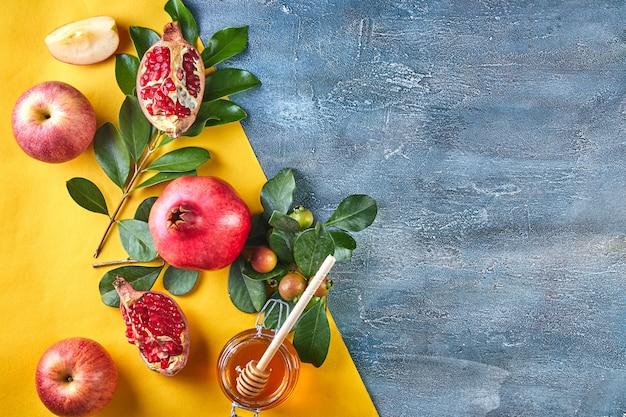 Traditionelle symbole: honigglas und frische äpfel mit granatapfel.