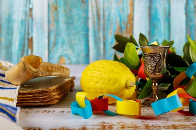 Traditionelle symbole jüdisches religiöses fest auf sukkot, das buchkippah tallitpapier bunte kettengirlande betet