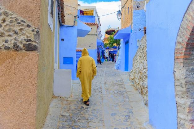 Traditionelle szene mit den leuten, die durch straße mit blau gehen, malte fassaden des dorfs von chefchaouen