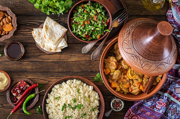 Traditionelle tajine-gerichte, couscous und frischer salat auf rustikalem holztisch. tajine lammfleisch und kürbis. ansicht von oben. flach liegen