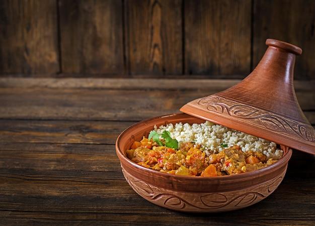 Traditionelle tajine-gerichte, couscous und frischer salat auf rustikalem holztisch. tajine lammfleisch und kürbis.