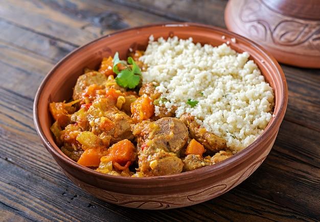 Traditionelle tajineteller, couscous und frischer salat auf rustikalem holztisch.