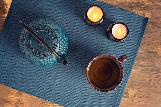 Traditionelle teezeremonie, teekanne und teetasse mit kräutern und trockenfrüchten, tee und kerzen. tisane entgiftung, entspannung, heilung, gesunde beruhigung, teezeitkonzept. draufsicht, flach liegen