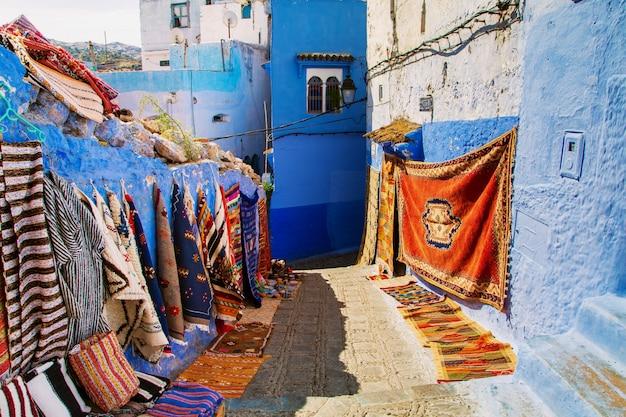 Traditionelle teppiche auf der blauen chefchaouen-straße.