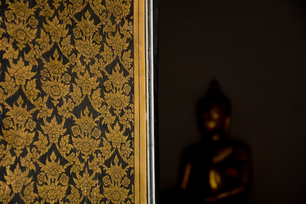 Traditionelle thailändische schöne kunst auf einem fenster am alten tempel