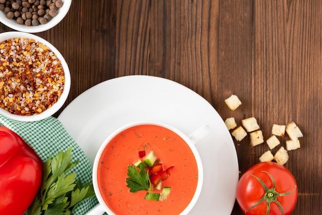 Traditionelle tomatensuppe der tomate auf einem hölzernen hintergrund mit verschiedenen gewürzen und kräutern. draufsicht.