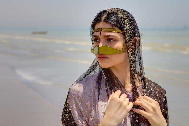 Traditionelle tracht des südlichen iran, schöne junge frau, die eine maske und hijab trägt