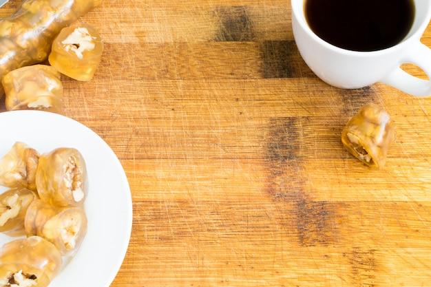 Traditionelle türkische freude lokum mit haselnuss draufsicht. süßes arabisches dessert und tasse schwarzen kaffee auf hölzernem hintergrund