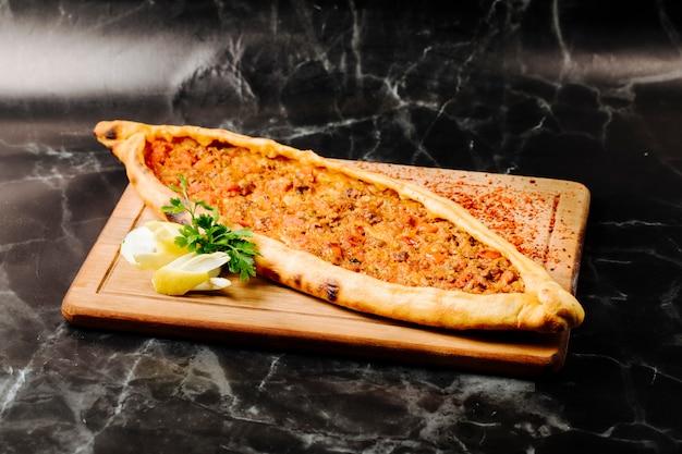 Traditionelle türkische pide mit dem fleisch angefüllt, zitrone und petersilie auf einem hölzernen quadratischen brett.