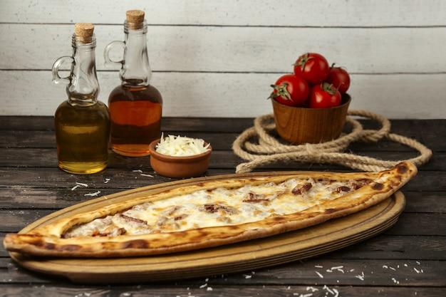 Traditionelle türkische pide mit fleisch und käse auf einem holzbrett